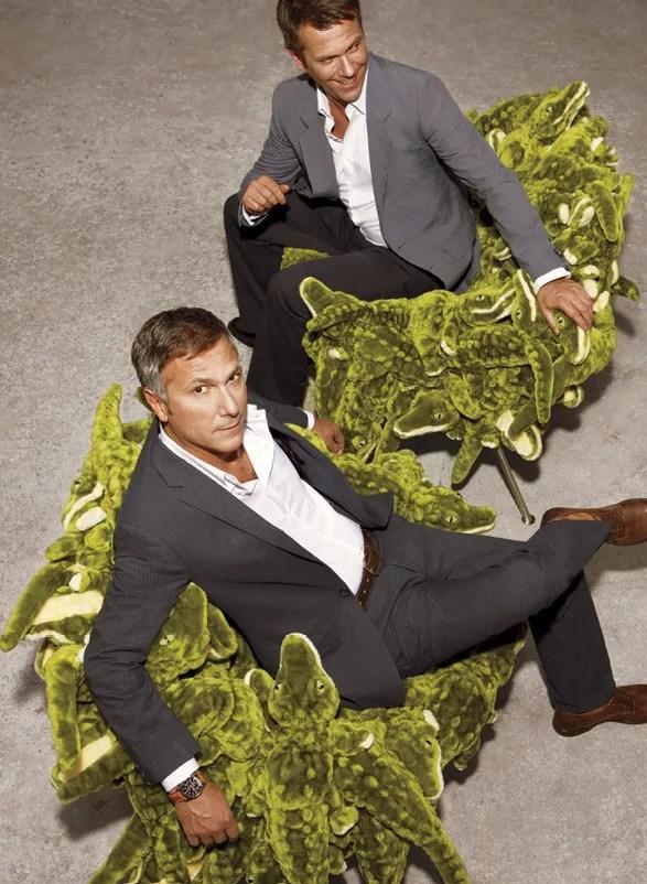 two people sitting on a chair of stuffed crocodiles