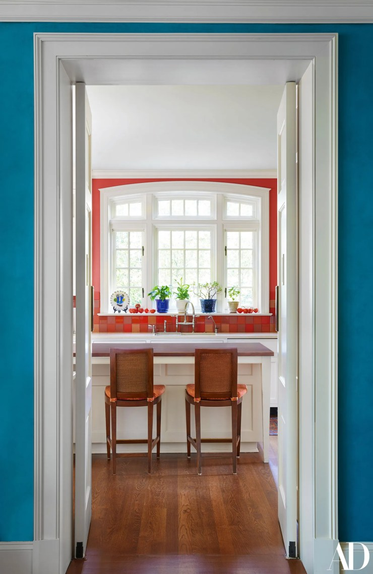 A peek into the homes kitchen where barstools face a window that looks out onto landscaped greenery. There had been a...