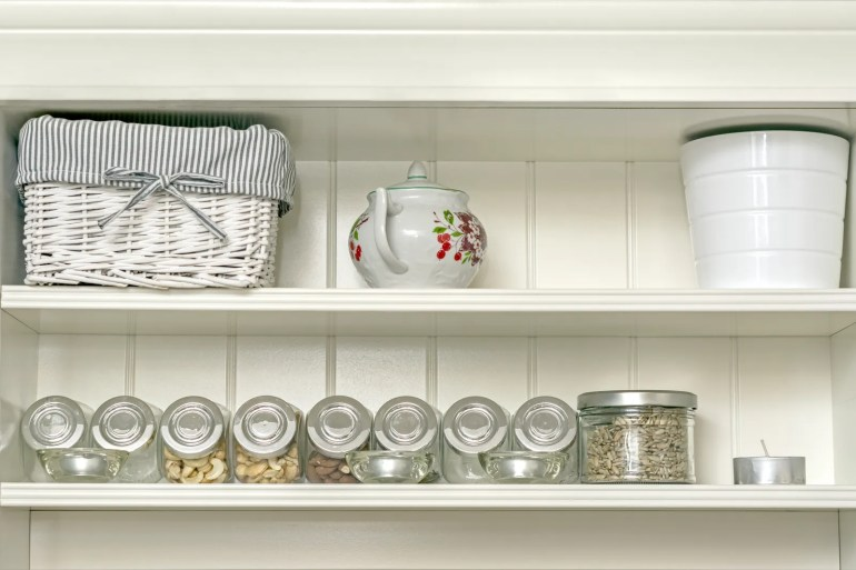 pKitchen interior with a fragment of a white shelf with a basket a sugar bowll and jars of ingredients.p