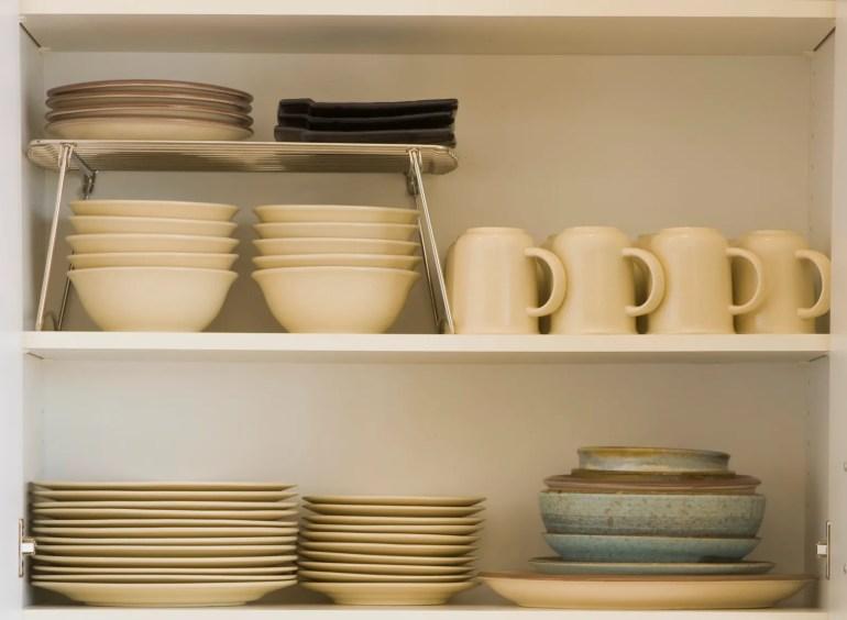 pKutfak tezgahı, tabak yığınları ile açık dolaplı kaseler ve fincanlar. p