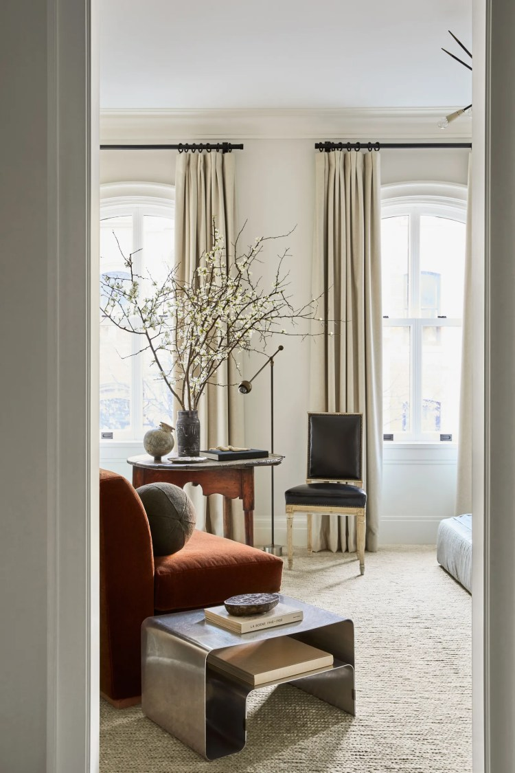 In the master bedroom a steel table by Maria Pergay sidles up to a chair by Nate Jeremiah for Living Spaces upholstered...