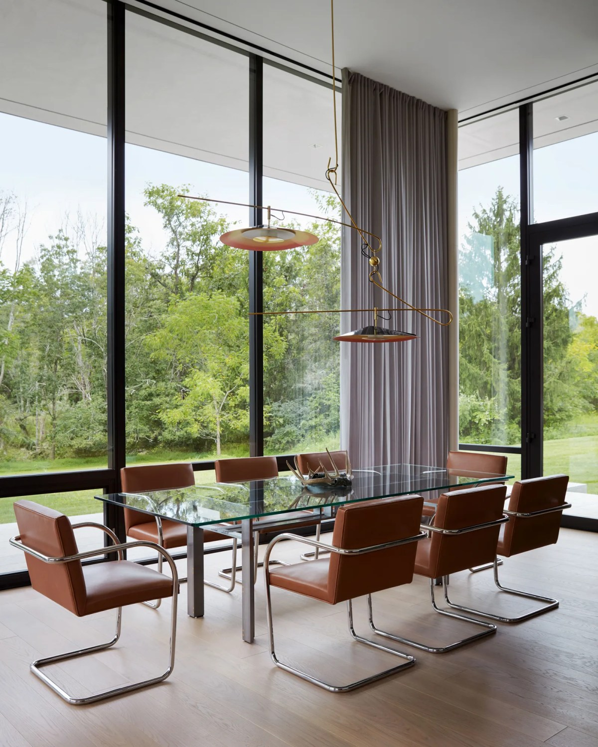 pKnoll leather Brno chairs surround a Carlo Scarpa table. A David Weeks enameled metal lighting fixture seems suspended...