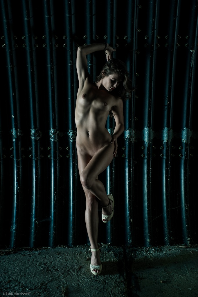 Séance photo nu en extérieur femme s'étire dans un tunnel