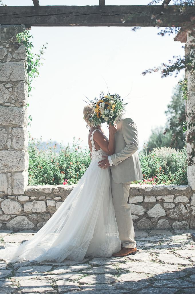 Les mariés se cachent derrière le bouquet de la mariée