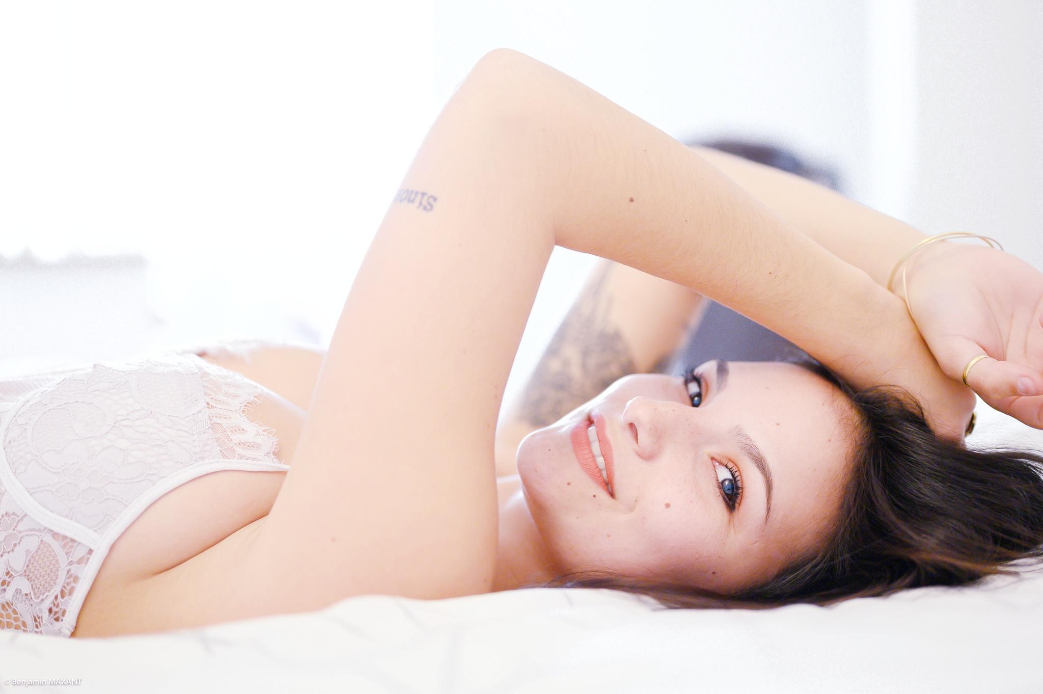 Séance photo boudoir avec Cléa body blanc allongée sur le lit