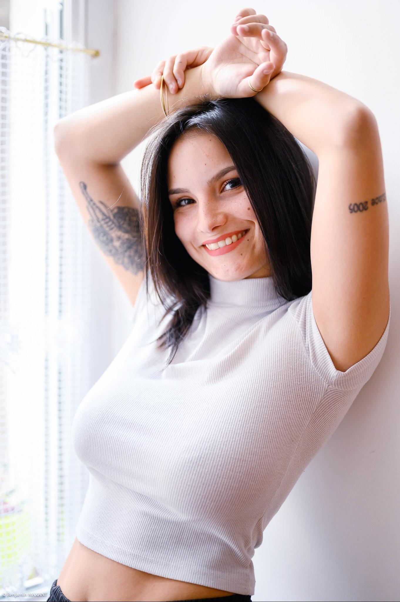 Séance photo boudoir avec Léa haut blanc moulant sourire tattoo