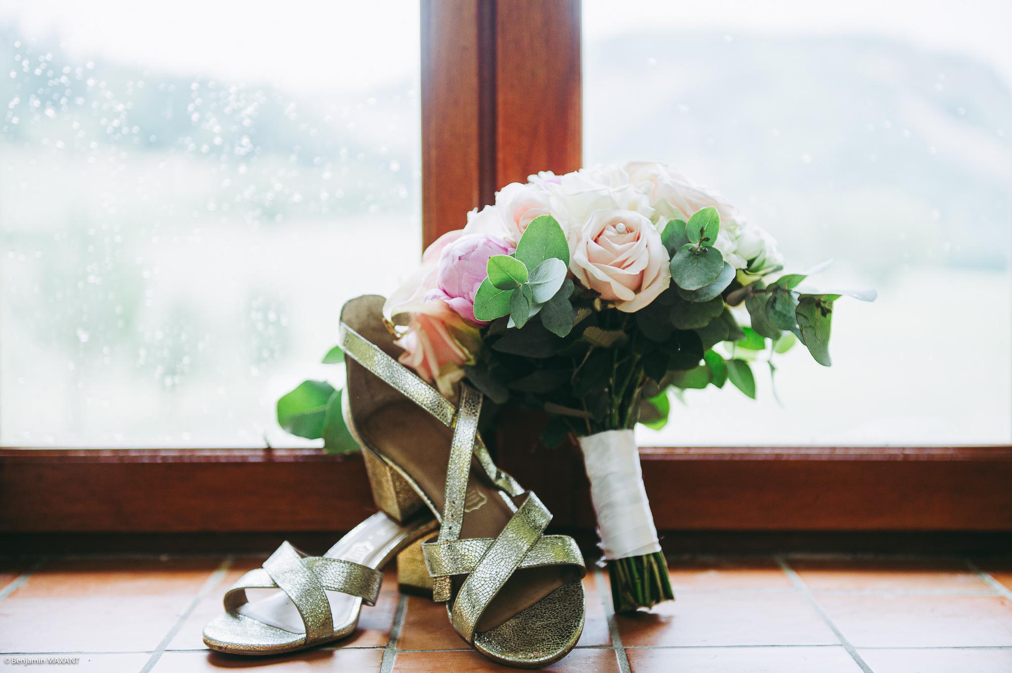 Le bouquet et les chaussure de la mariée posés devant une fenêtre
