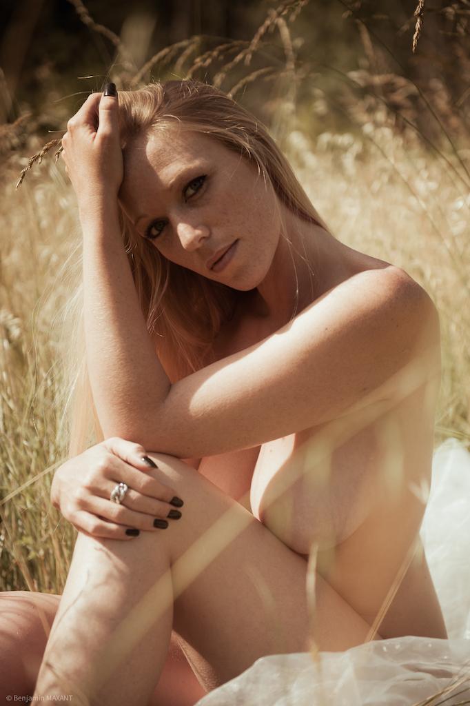 Séance photo nu en extérieur modèle blonde assise dans les hautes herbes