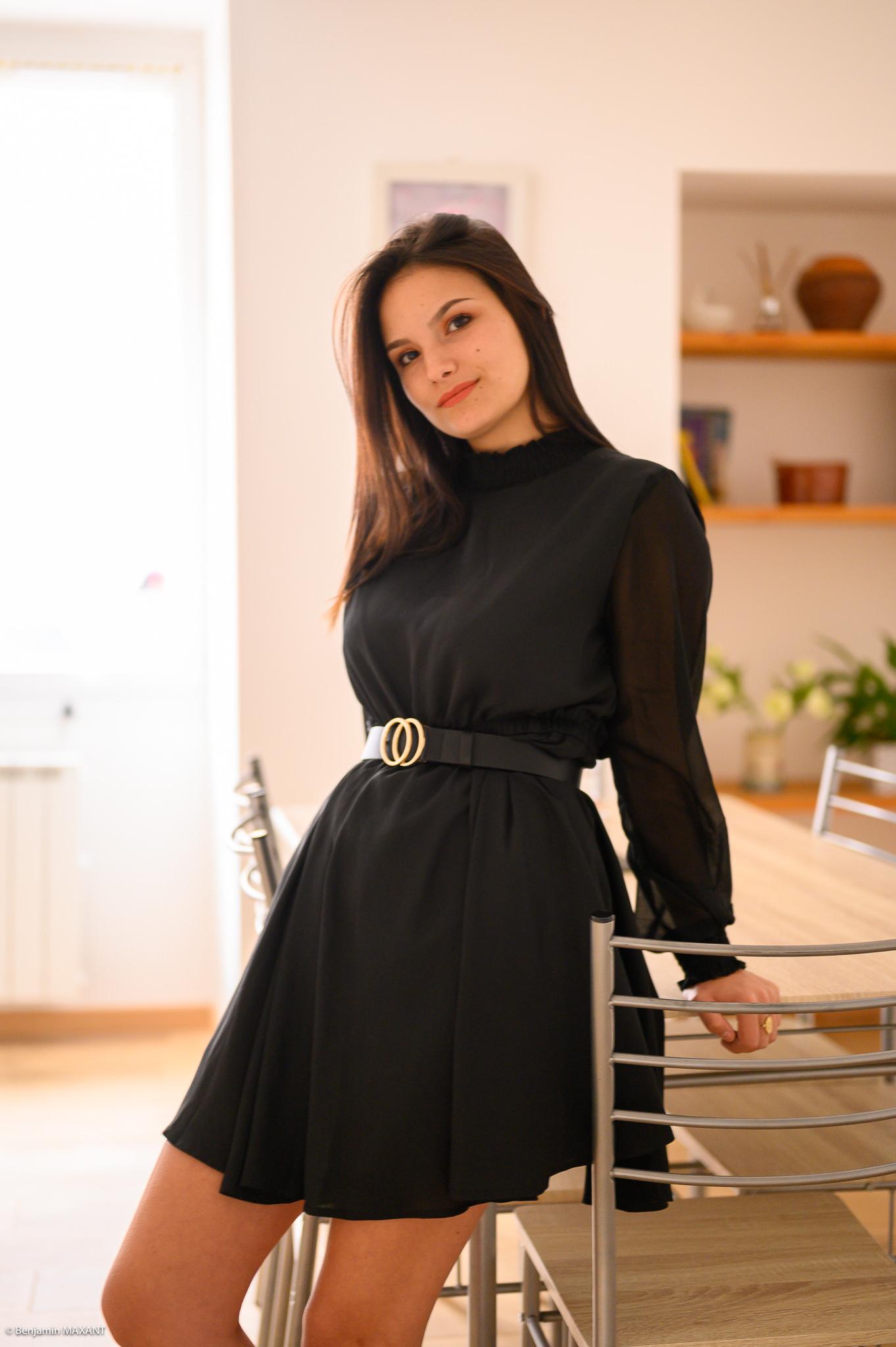 Séance photo boudoir robe noire alle à manger assise contre la table