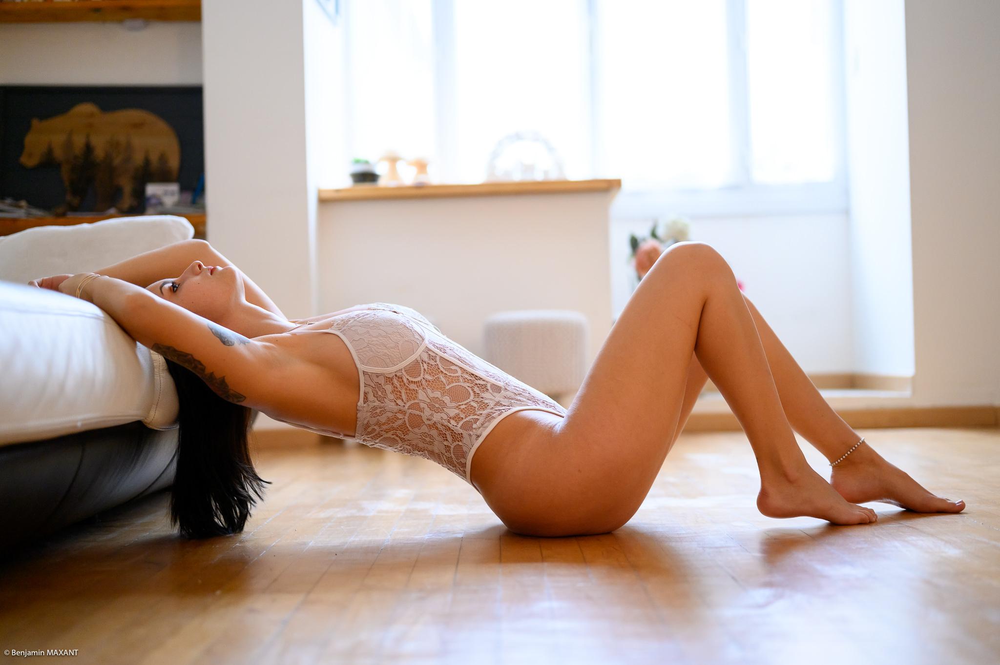 Séance photo boudoir body blanc alongée sur le parquet contre le canapé