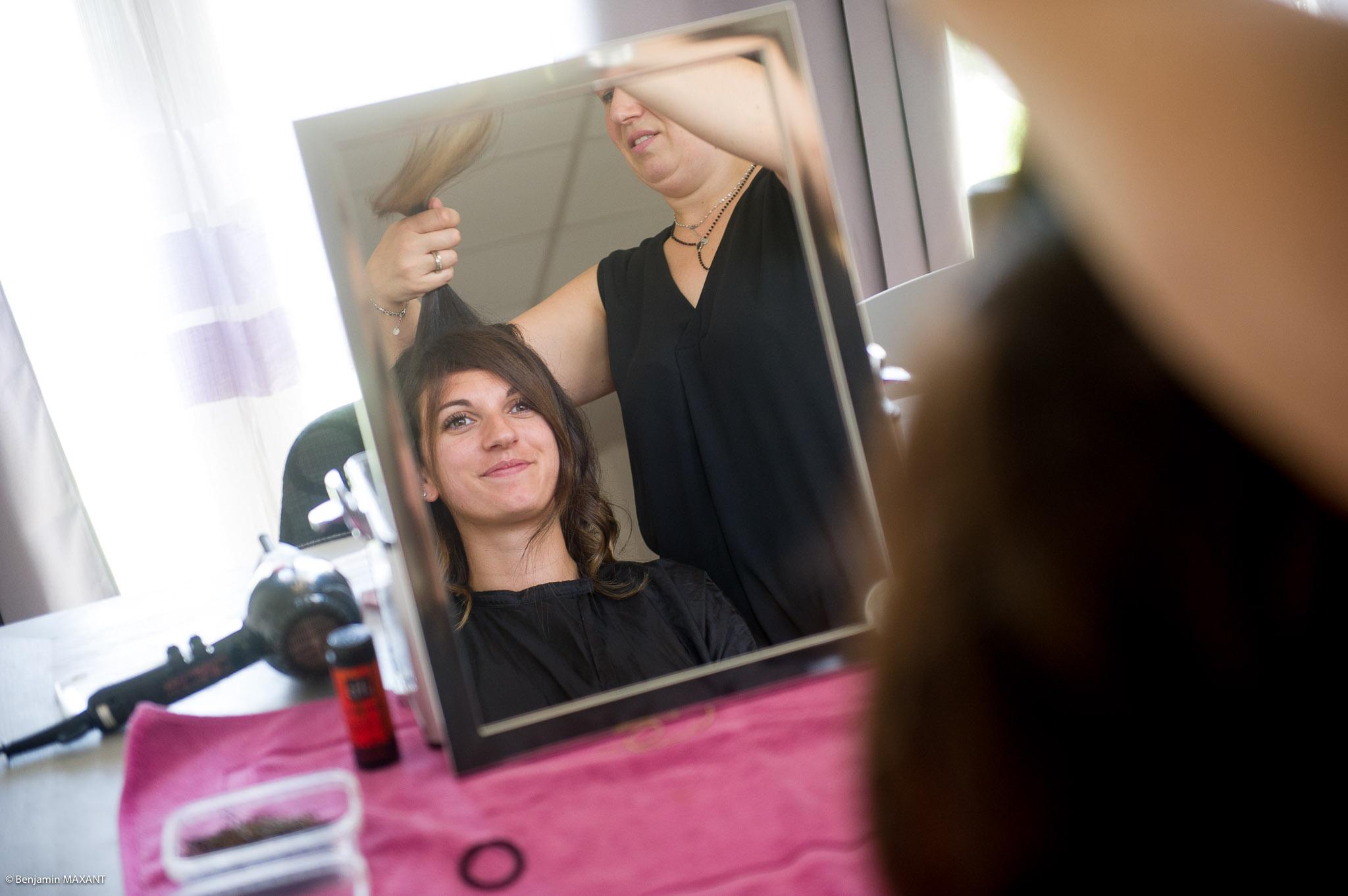 Préparation de Julie la mariée : la coiffure devant le miroir