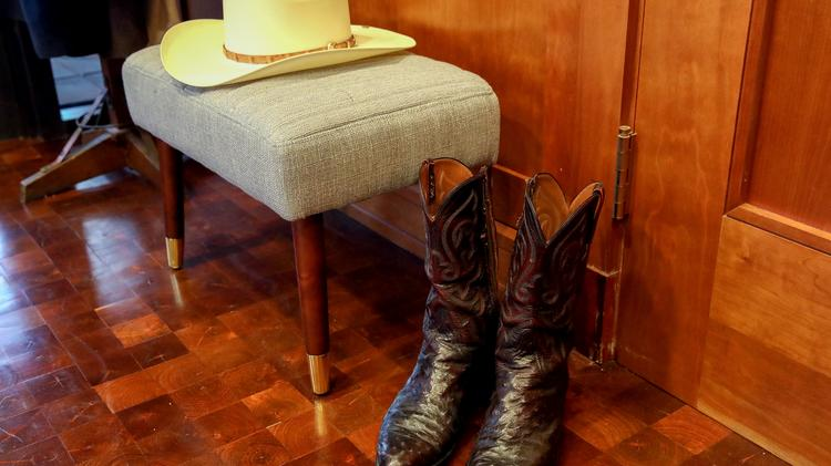 A cowboy hat and boots are prepared for Red McCombs at his office.