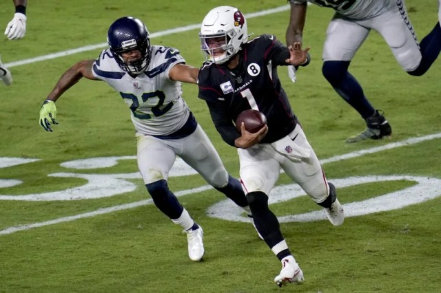 Arizona Cardinals quarterback Kyler Murray (1) eludes the reach of Seattle Seahawks cornerback Quinton Dunbar (22) during the first half of an NFL football game, Sunday, Oct. 25, 2020, in Glendale, Ariz. (AP Photo/Ross D. Franklin)