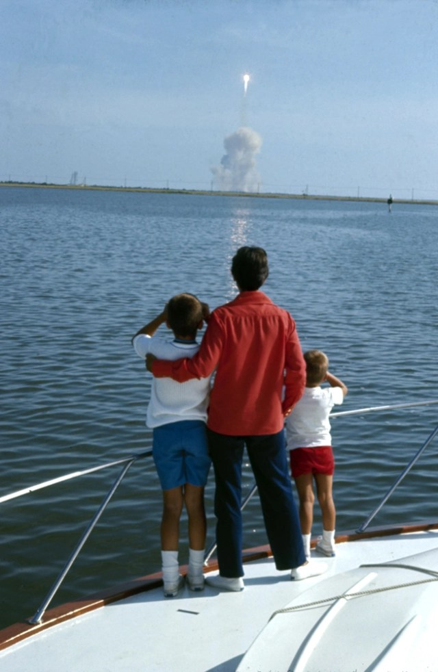 Jan Armstrong, wife of Apollo 11 astronaut Neil Armstrong, gazing upon white trail in sky of Apollo 11 blastoff, from boat, with son. Photo: TIME.