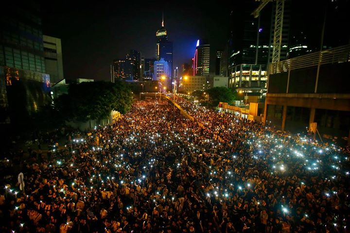 Protesters hold their mobile phones as they block the main street to the financial Central district, outside the government headquarters, in Hong Kong, September 29, 2014.  [REUTERS/Carlos Barria]