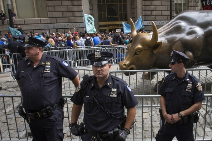 New York City police officers stand guard in front of the Charging Bull sculpture.