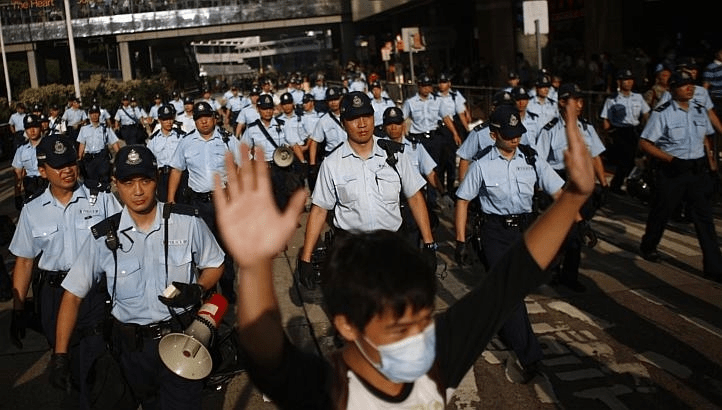A protester raises his arms as police officers try to disperse the crowd near the government headquarters in Hong Kong, September 29, 2014.  [REUTERS/Carlos Barria]