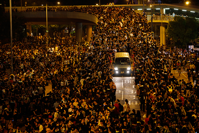 A vehicle drives among protesters blocking the main street to the financial Central district, outside the government headquarters, in Hong Kong September 29, 2014.  [REUTERS/Carlos Barria]