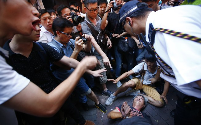 A man, who a witness said started a fight with several pro-democracy protesters, lies on the ground with hands tied by the protesters near a barricade on a main street in Hong Kong's Mongkok shopping district October 4, 2014. [Reuters]