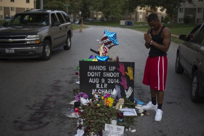 Ken Kendricks Jr., a nearby resident, puts his hands together in prayer at a makeshift memorial at the site where unarmed teen Michael Brown was shot dead in Ferguson, Missouri Aug. 22, 2014. Reuters/Adrees Latif