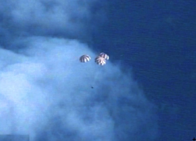 Dec. 5, 2014 –- Following more than four hours in Earth orbit, NASA's Orion spacecraft is seen from an unpiloted aircraft as it descends under three massive red and white main parachutes. Splashdown in the Pacific Ocean will take place at less than 20 mph. It will be recovered by the USS Anchorage, a landing platform-dock, or LPD, ship. Photo: NASA