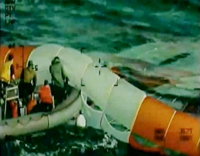 Dec. 5, 2014 –- Following splashdown of the Orion crew module, U.S. Navy crews from the USS Anchorage began recovering the three parachutes while other teams began safing the spacecraft. After lines are attached, Orion will be towed into the well deck of the recovery ship, USS Anchorage. Photo: NASA