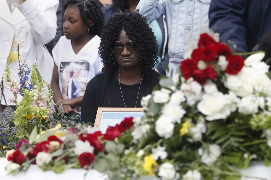 Gloria Darden, mother of Freddie Gray who died following an arrest by the Baltimore police department, sits by the casket at his burial at Woodlawn Cemetery in Baltimore, Maryland April 27, 2015.  [REUTERS/Shannon Stapleton]