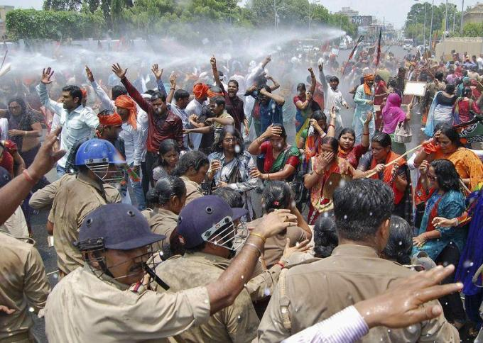 Supporters of Bharatiya Janata Party (BJP) shout slogans as police use a water cannon to stop them from moving towards the office of Akhilesh Yadav, the chief minister of Uttar Pradesh, during a protest against recent rape and hanging of two girls, in Lucknow in 2014. REUTERS/Pawan Kumar