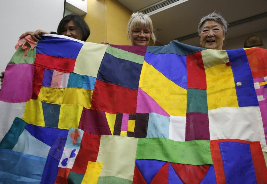 NGO activist Choi Ai-young (R) and other members of the WomenCrossDMZ group pose with Korea's traditional patchwork before the group leaves for North Korea's capital Pyongyang, at a hotel in Beijing, China, May 19, 2015. REUTERS/Kim Kyung-Hoon