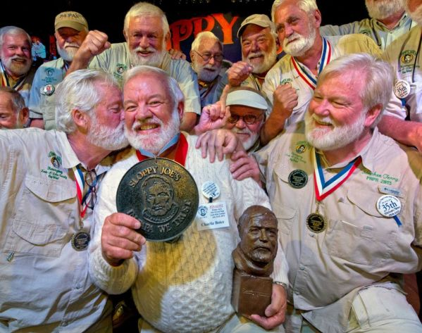 """In this Saturday, July 25, 2015 photo provided by the Florida Keys News Bureau, Charlie Boice, center, is congratulated by previous victors after winning the 2015 """"Papa"""" Hemingway Look-Alike Contest at Sloppy Joe's Bar in Key West, Fla. Boice finally won the contest after trying for 15 years, beating out 121 other entrants following two preliminary rounds, a semi-final and two final rounds. The competition was a facet of the island's annual Hemingway Days festival that ends Sunday, July 26. Planting a playful snook on Boice is Wally Cox, left, the 2014 winner. (Andy Newman/Florida Keys News Bureau)"""