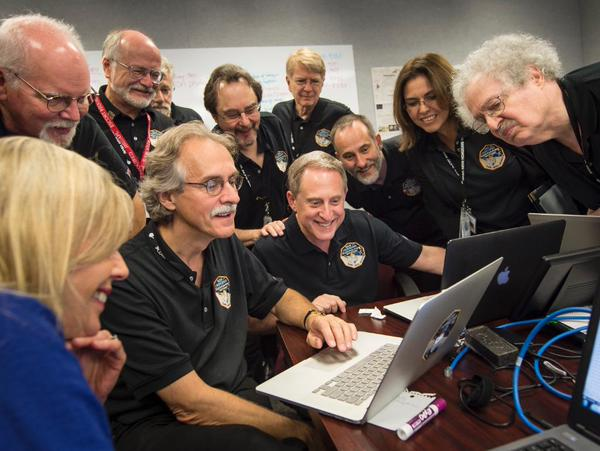 In the Mission Control center, NASA's New Horizons operations team celebrates a successful visit to Pluto by the space probe.