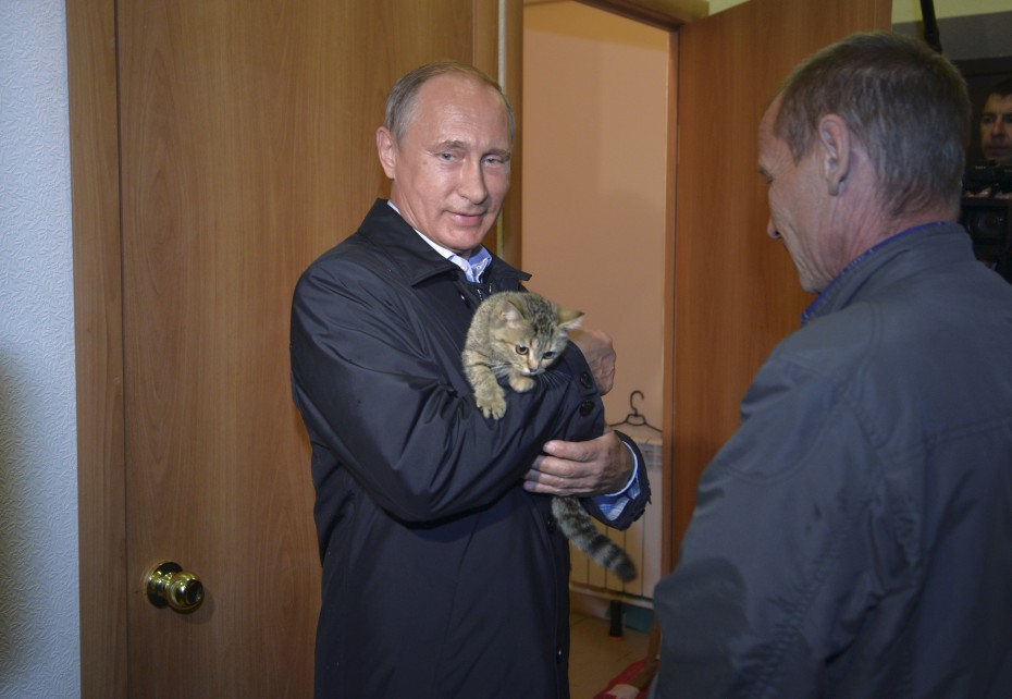 Putin holds a cat while inspecting reconstruction of houses for people who suffered from wildfires in the village of Krasnopolye at the Siberian Khakasiya region, Russia, September 4, 2015. [Reuters]