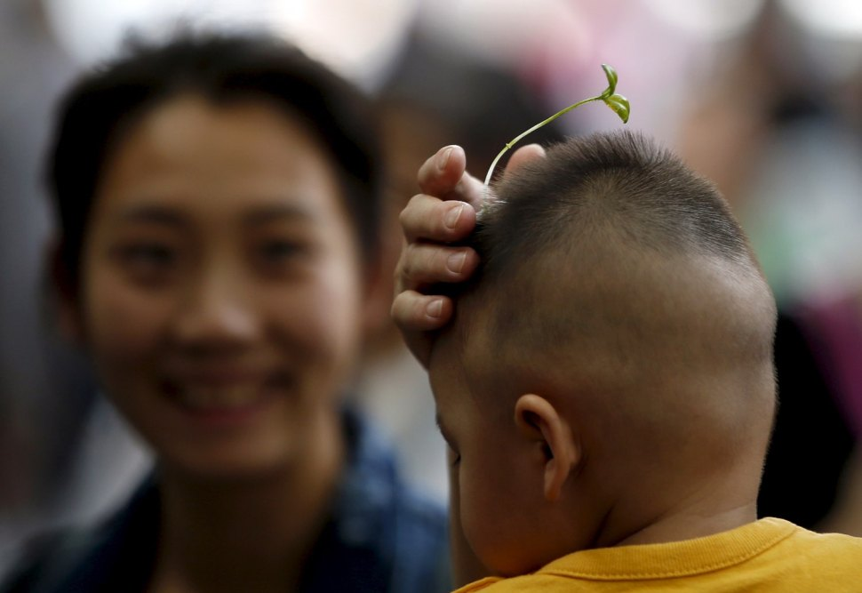 A woman tries a sprout-like hairpin on a baby in Beijing, China. REUTERS