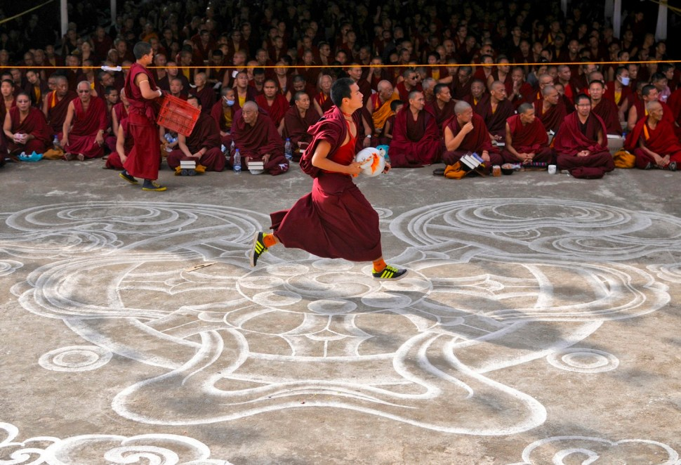 A young Buddhist monk runs past other monks to fetch butter tea to be served to attendees of the Jangchup Lamrim teachings conducted by the exiled Tibetan spiritual leader the Dalai Lama (unseen) at the Gaden Jangtse Thoesam Norling Monastery in Mundgod in the southern Indian state of Karnataka December 25, 2014. REUTERS/Abhishek N. Chinnappa (INDIA - Tags: RELIGION) - RTR4J8CD