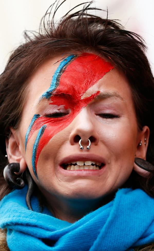 A woman wearing Ziggy Stardust-style make-up reacts as she visits a mural of David Bowie in Brixton,