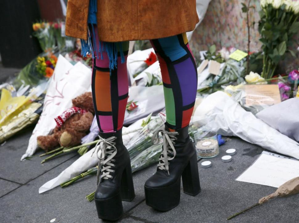 A woman stands next to flowers and tributes as she visits a mural of David Bowie in Brixton