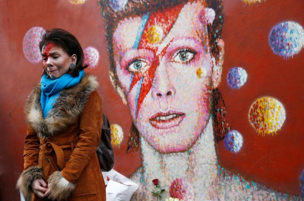 A woman wearing Ziggy Stardust-style make-up reacts as she visits a mural of David Bowie in Brixton, south London