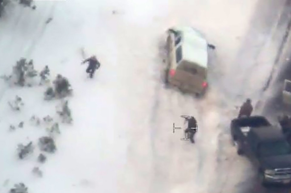 Aerial video released by the FBI January 28, 2016 shows a law enforcement officer (C) pointing a weapon at a man (L) who had just stepped out of the white pickup truck at a police roadblock January 26 near Burns, Oregon.  The FBI released video showing one of the men occupying an Oregon wildlife refuge reach for his jacket pocket before he was shot dead by law enforcement after speeding away from a traffic stop where the group's leader was arrested.  Authorities said 54-year-old Robert LaVoy Finicum, a rancher from Arizona who acted as a spokesman for the occupiers at the Malheur National Wildlife Refuge, was armed when he was stopped by police and killed on Tuesday afternoon.