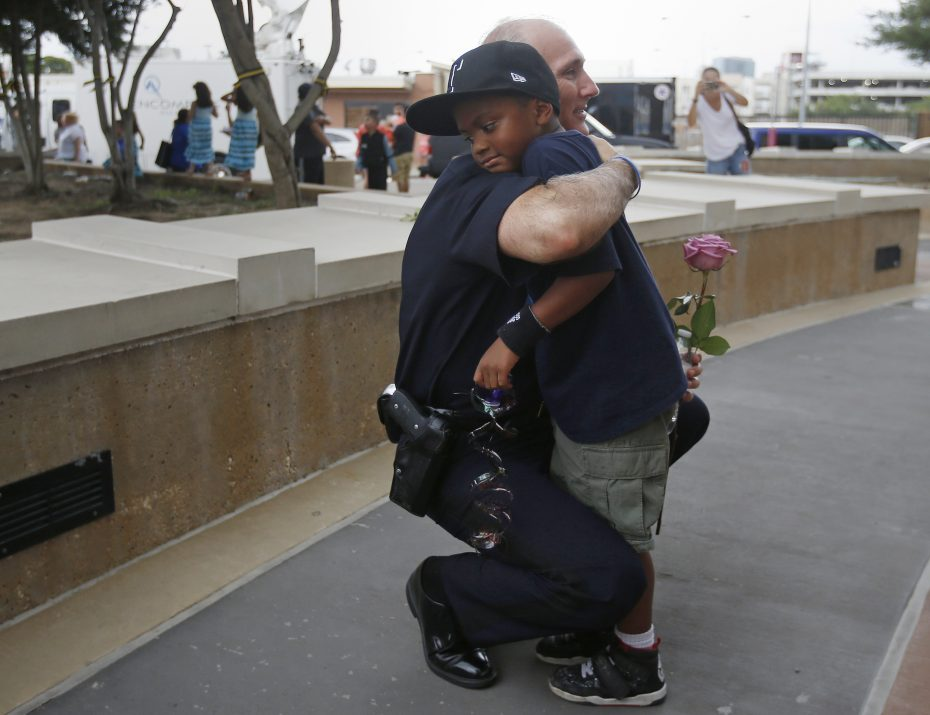 A Dallas Police officer hugs a child who came to pay respects at a makeshift memorial at Dallas Police Headquarters following the multiple police shootings in Dallas, Texas, U.S., July 9, 2016.   REUTERS/Carlo Allegri