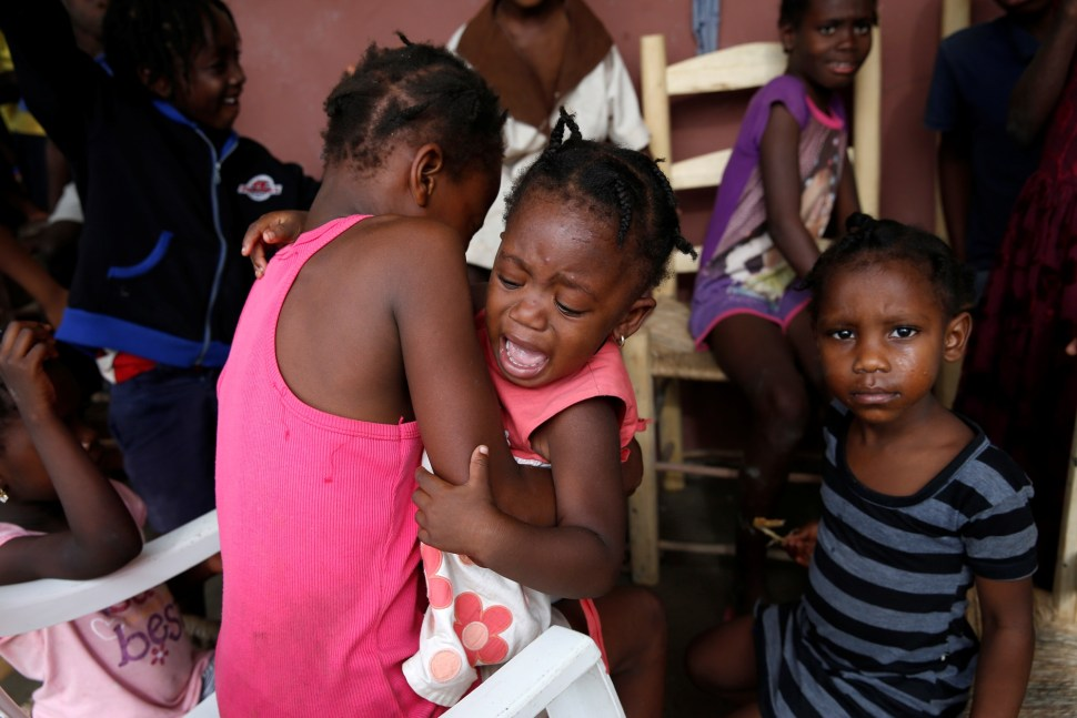 A girl cries as she stays with her relatives at a partially destroyed school after Hurricane Matthew passes Jeremie, Haiti, October 5, 2016. REUTERS