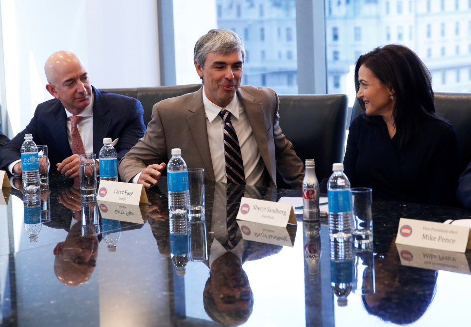 Larry Page (C), CEO and Co-founder of Alphabet, speaks while Sheryl Sandberg, Chief Operating Officer of Facebook (R), and Amazon CEO Jeff Bezos look on during a meeting with U.S. President-elect Donald Trump and technology leaders at Trump Tower in New York U.S., December 14, 2016. REUTERS
