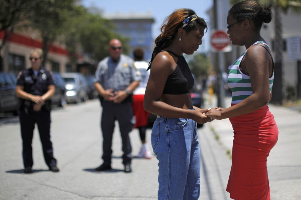 Mourners hold hands as they pause outside a memorial at Morris Brown African Methodist Episcopal Church. BRIAN SNYDER/REUTERS