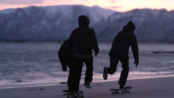 Watch skateboarders skate on frozen sand