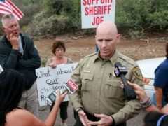 Pinal County Head Sheriff Paul Babeu speaks with anti-immigration activists and the media during a protest along Mt. Lemmon Road in anticipation of buses carrying illegal immigrants on Jully 15, 2014 in Oracle, Arizona. About 300 protesters lined the road waiting for a busload of illegal immigrants who are to be housed at a facility in Oracle.