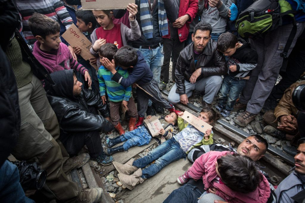 IDOMENI, GREECE - MARCH 12: Children lie on railway tracks leading to Macedonia as they protest and call for the border to be opened at the Idomeni refugee camp on the Greek Macedonia border on March 12, 2016 in Idomeni, Greece. The decision by Macedonia to close its border to migrants on Wednesday has left thousands of people stranded at the Greek transit camp. The closure, following the lead taken by neighbouring countries, has effectively sealed the so-called western Balkan route, the main migration route that has been used by hundreds of thousands of migrants to reach countries in western Europe such as Germany. Humanitarian workers have described the conditions at the camp as desperate, which has been made much worse by recent bouts of heavy rain. (Photo by Matt Cardy/Getty Images)