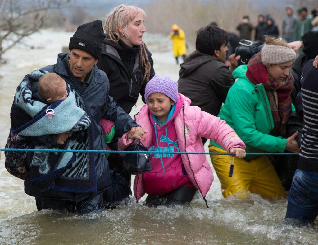 IDOMENI, GREECE - MARCH 14: Migrants cross a river after leaving the Idomeni refugee camp on March 14, 2016 in Idomeni, Greece. The decision by Macedonia to close its border to migrants on Wednesday has left thousands of people stranded at the Greek transit camp. The closure, following the lead taken by neighbouring countries, has effectively sealed the so-called western Balkan route, the main migration route that has been used by hundreds of thousands of migrants to reach countries in western Europe such as Germany. Humanitarian workers have described the conditions at the camp as desperate, which has been made much worse by recent bouts of heavy rain. (Photo by Matt Cardy/Getty Images)