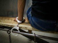 View of an unidentified male suspect handcuffed to a bench in the Southeast Community Police Station, Los Angeles, California, April 24, 2015. The man had been arrested for solicitation of prostitution in the South Figueroa Street corridor by the LAPD's Human Trafficking Task Force. (Photo by Robert Nickelsberg/Getty Images)
