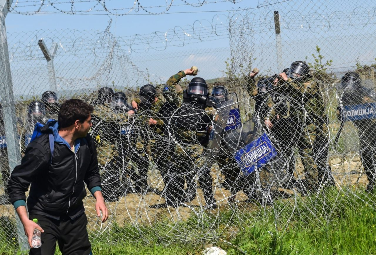 Macedonian police resort to throwing stones at migrants to stop them crossing the border (BULENT KILIC/AFP/Getty Images)
