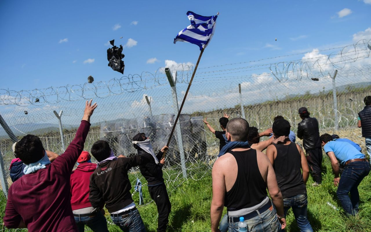 A man waves a Greek flag as others clash with Macedonian soldiers (BULENT KILIC/AFP/Getty Images)