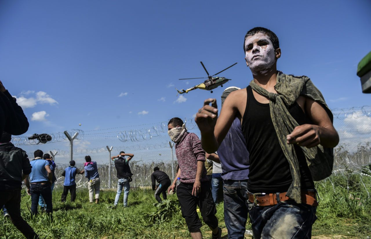 Refugees and migrants clash with Macedonian soldiers during a protest for the reopening of the border near their makeshift camp in the northern Greek border village of Idomeni, on April 10, 2016. Dozens of people were hurt when police fired tear gas on a group of migrants as they tried to break through a fence on the Greece-Macedonia border, the medical charity Doctors without Borders (MSF) said. A plan to send back migrants from Greece to Turkey sparked demonstrations by local residents in both countries days before the deal brokered by the European Union is set to be implemented. / AFP / BULENT KILIC (Photo credit should read BULENT KILIC/AFP/Getty Images)